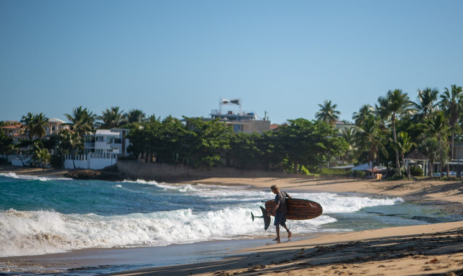walking on a beach with a hydrofoil surfboard